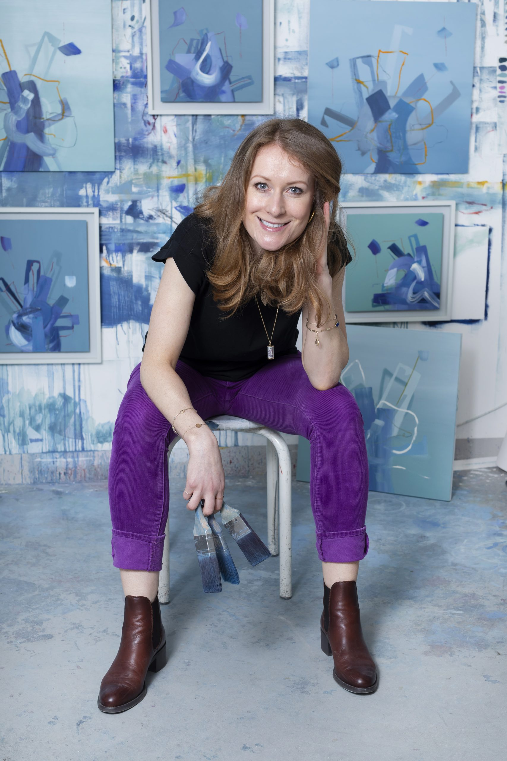 Abstract painter aisling drennan in her studio holding paintbrushes with green & blue paintings in the background. Abstract art painting, Abstract art canvas, Abstract oil painting, Contemporary painting, Oil painting, Original oil painting, Painting, paintings, art studio, abstract painting, art collector, abstract art collector, painting collector Abstract artists, Modern art, Modern wall art, Modern abstract, artists, Female abstract artists, Abstract artists uk, Abstract artists ireland, Irish artist, female artist, Irish abstract artist, Aisling Drennan, Aisling drennan painting, Aisling drennan, art, abstract art uk, irish abstract art, female abstract artists