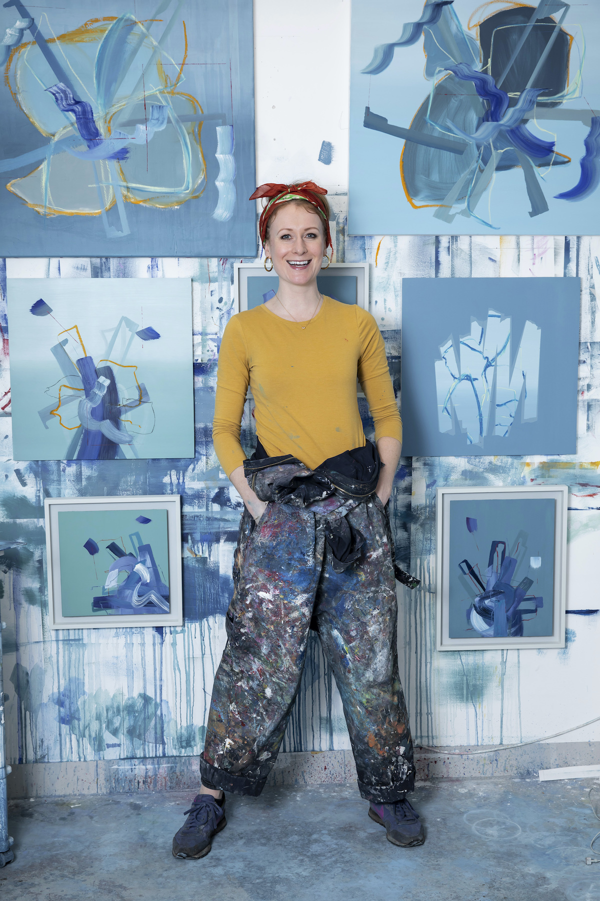 abstract art artist aisling drennan in her studio in london with blue abstract paintings and green abstract paintings